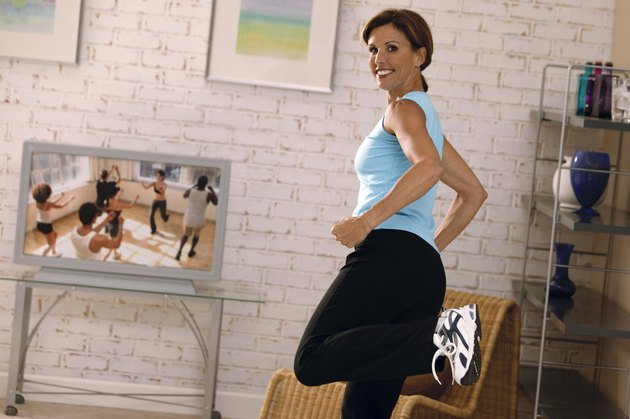 Woman jogging while watching exercise video