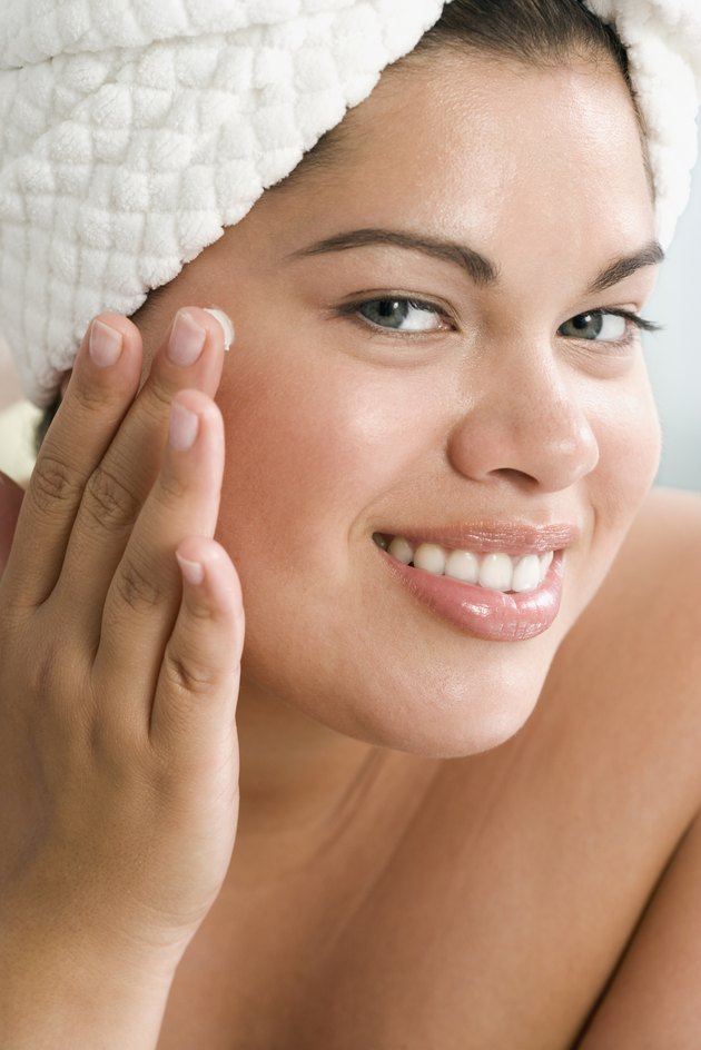 Close up of Hispanic woman applying face lotion