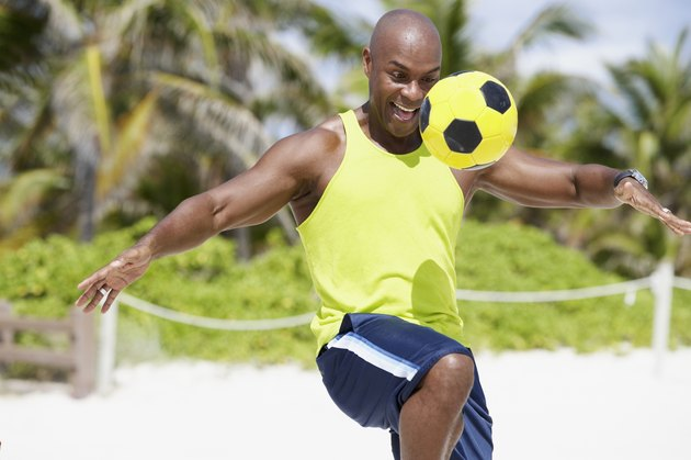 African American man bouncing soccer ball on knee