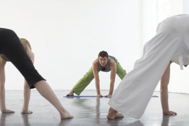 Yoga teacher at front of class demonstrating prasarita padottanasana