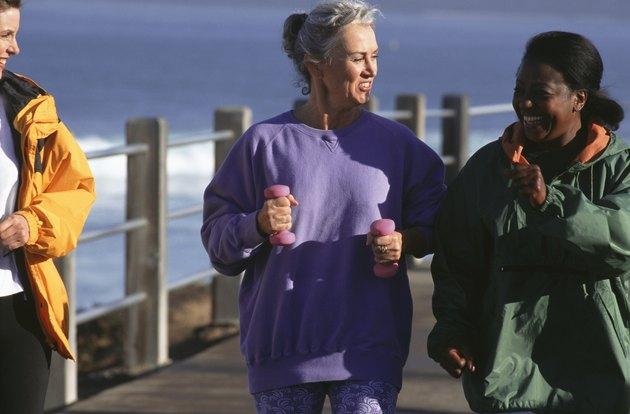 Three women walking along pier, talking