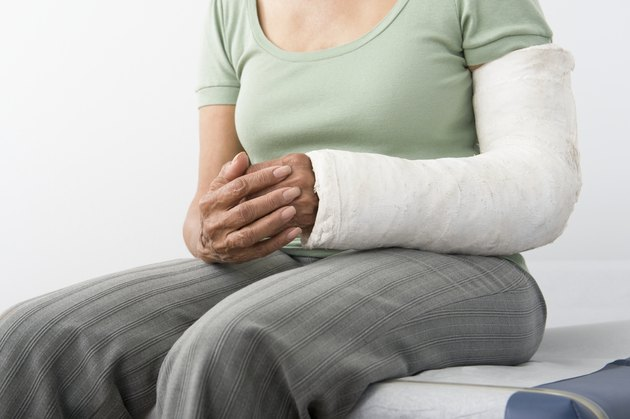 Senior woman sits with plastercast on broken arm, mid-section