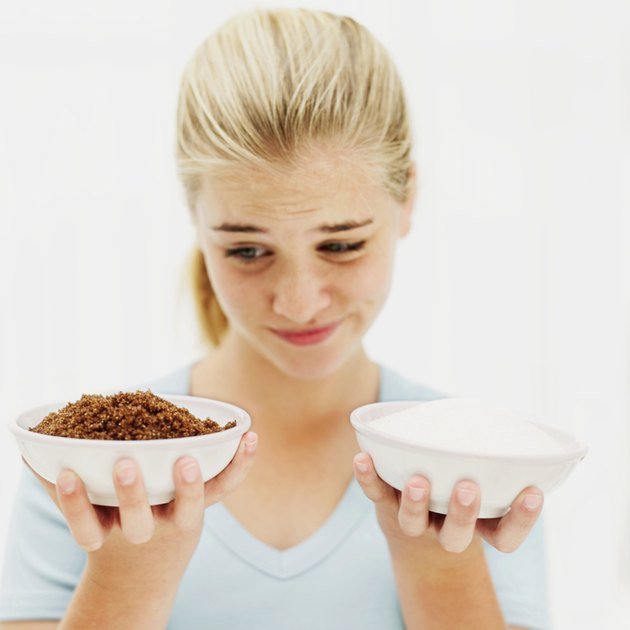 close-up of a teenage girl holding two bowls with white and brown sugar