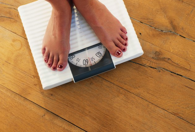 Woman standing on weight scale, low section