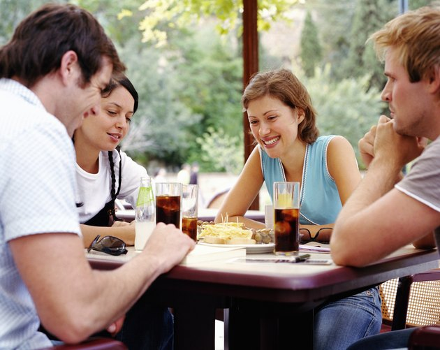 Two couples having drinks at outdoor cafe, smiling