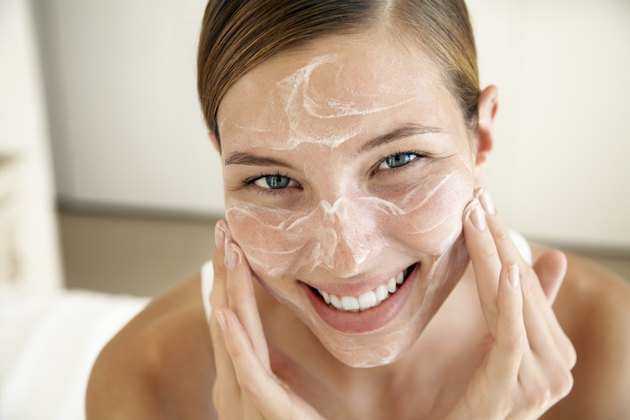 Smiling Young Woman Applying Face Cream