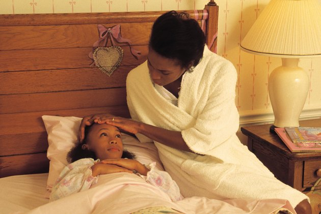 Mother caring for sick daughter in bed