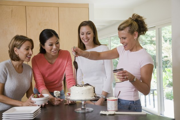 Women in kitchen preparing a cake