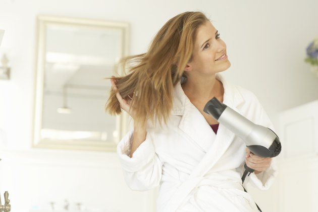 Young woman blowdrying hair, wearing dressing gown, smiling