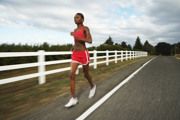 Young woman jogging along country road (blurred motion)