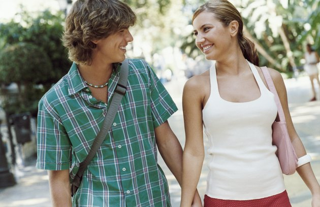 Smiling Young Couple Walking Hand in Hand