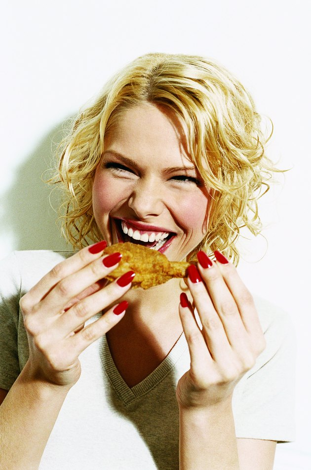 Portrait of a Smiling, Young Woman Eating a Deep Fried Chicken Drumstick