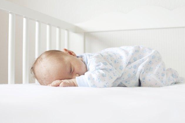 newborn lying on his tummy in crib