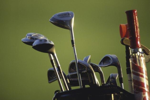 Close-up of golf clubs and an umbrella