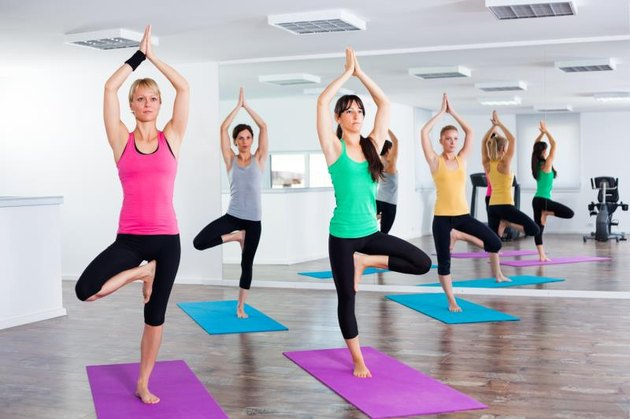 Four girls practicing yoga, Yoga-Tree pose/Vrikshasana