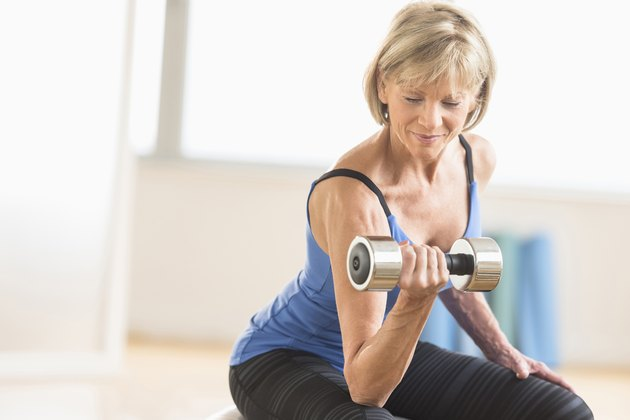 Mature Woman Lifting Dumbbell At Home