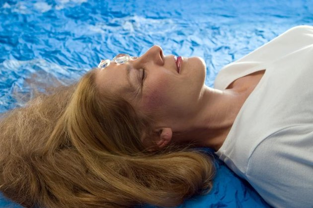 woman laying relaxed during a treatment with a 2 mountain crystals on her third eye, chakra. It is a kind of energy healing