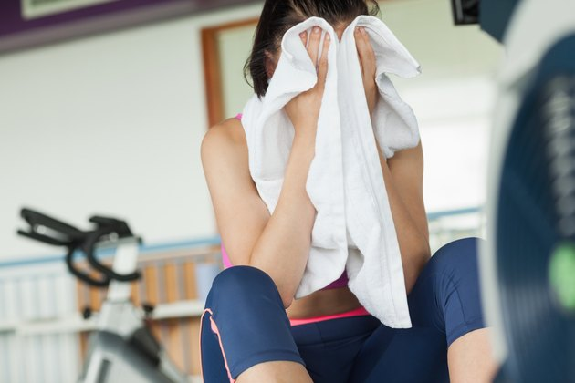 Tired young woman wiping face while working on row machine