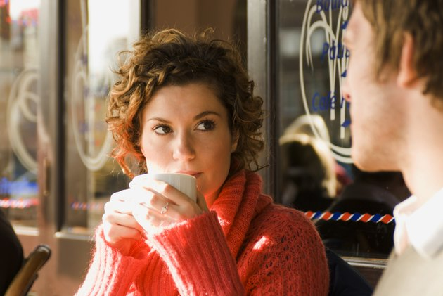 Young woman drinking a cup of tea in a sidewalk cafe