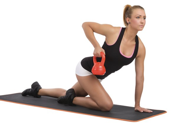 Female Fitness Instructor On Exercise Mat With Kettlebell