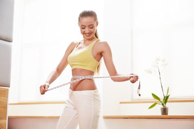 Diet. Dieting concept. Woman in Sportswear Measuring Her Waist