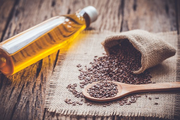 Flax seeds in the sack and oli on wooden background