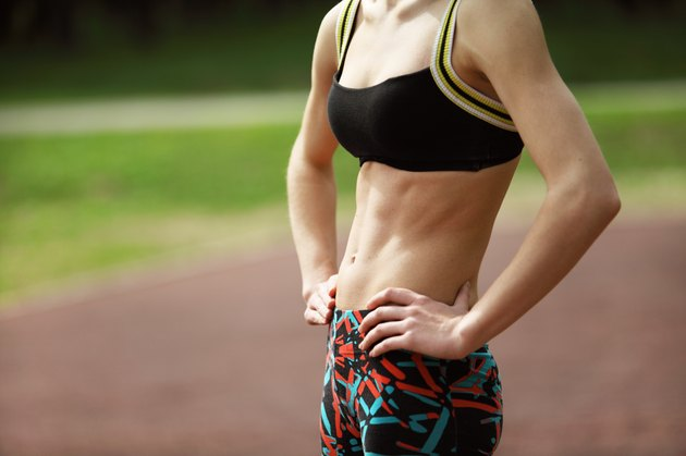 Athletic young woman with tight defined abs in stomach