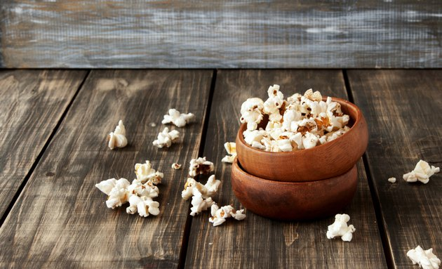 popcorn in wooden bowl on a wood background, selective focus