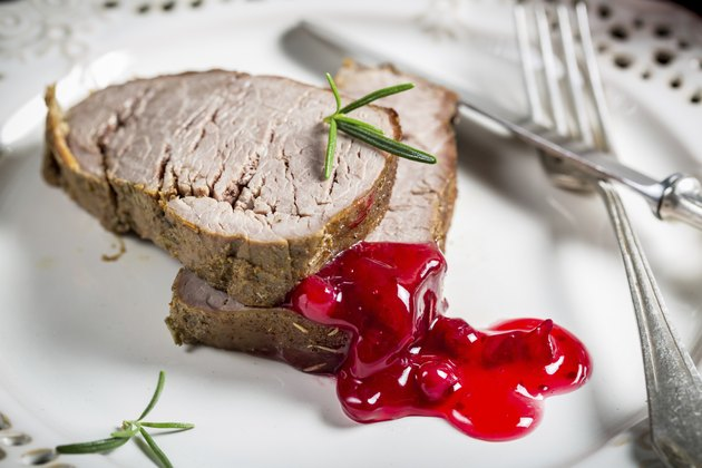Venison served with cranberry sauce on white plate