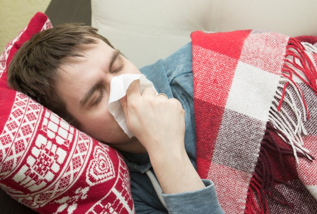 Man with cold lying and sneezing in tissue