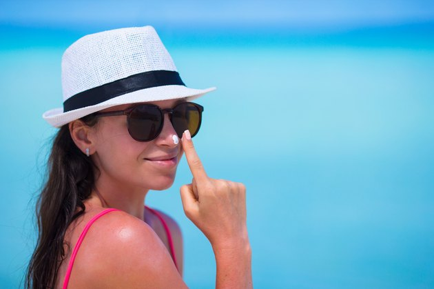 Young woman applying suntan lotion on her nose on beach