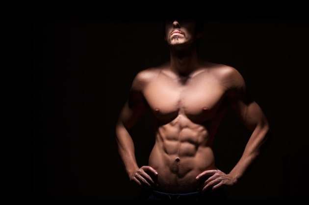 Muscular man with dark background.