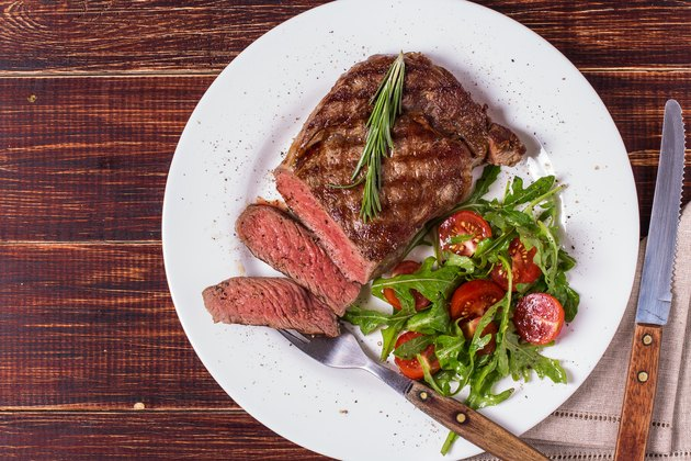 Ribeye steak with arugula and tomatoes.