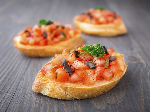 Tomato bruschetta topped with olive