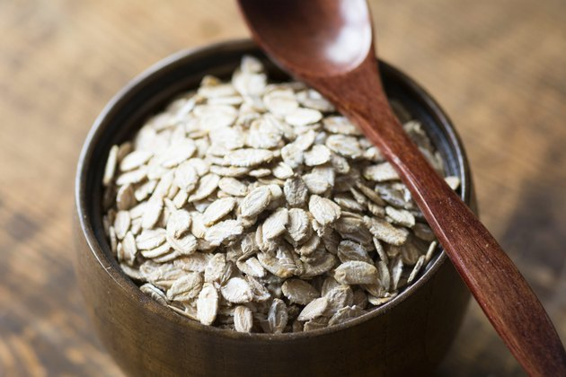 Organic rolled oats in wooden bowl with wooden spoon