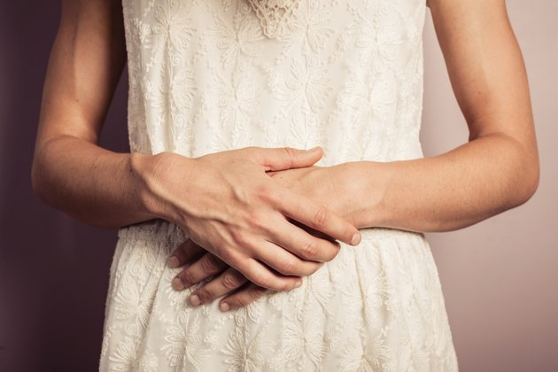 Young woman in white dress with stomach pains