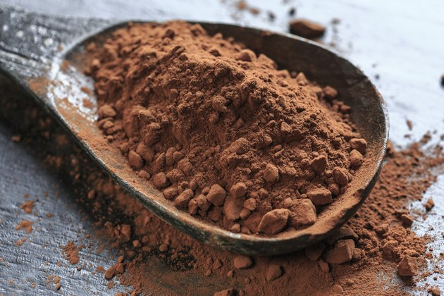 A large wooden spoonful of cacao powder.