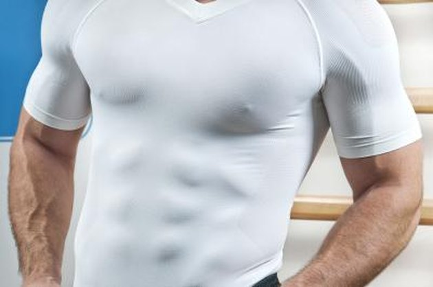 Muscular torso through white shirt in gym.