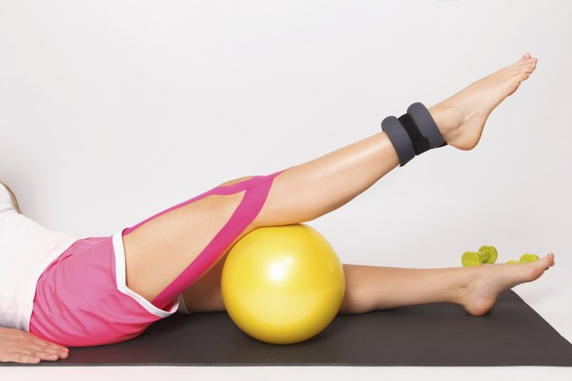 Therapy for leg injury with ball and kinesio tape