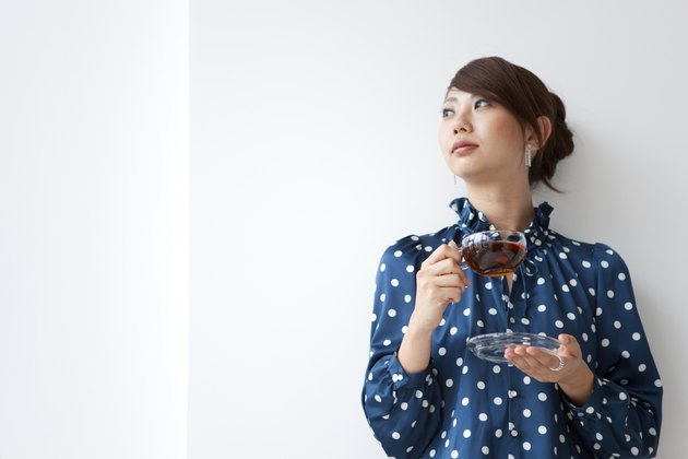 Young woman leaning on wall and looking away, holding cup of tea, white background, copy space