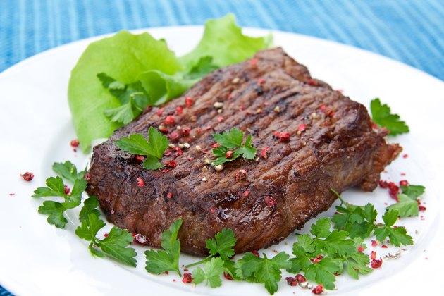 roast big steak on green dish close up