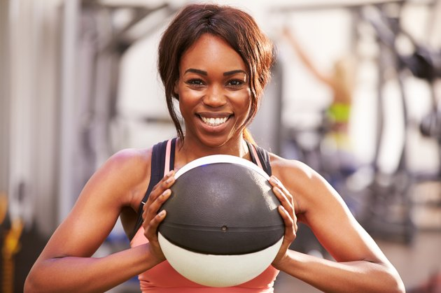 Portrait of woman holding a medicine ball at a gym