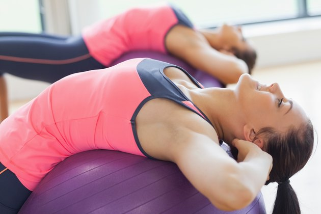 Two fit young women stretching on fitness balls in gym