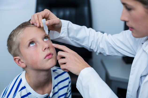 Female optometrist putting eye drop in young patient eyes