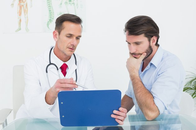 Male doctor discussing reports with patient at desk