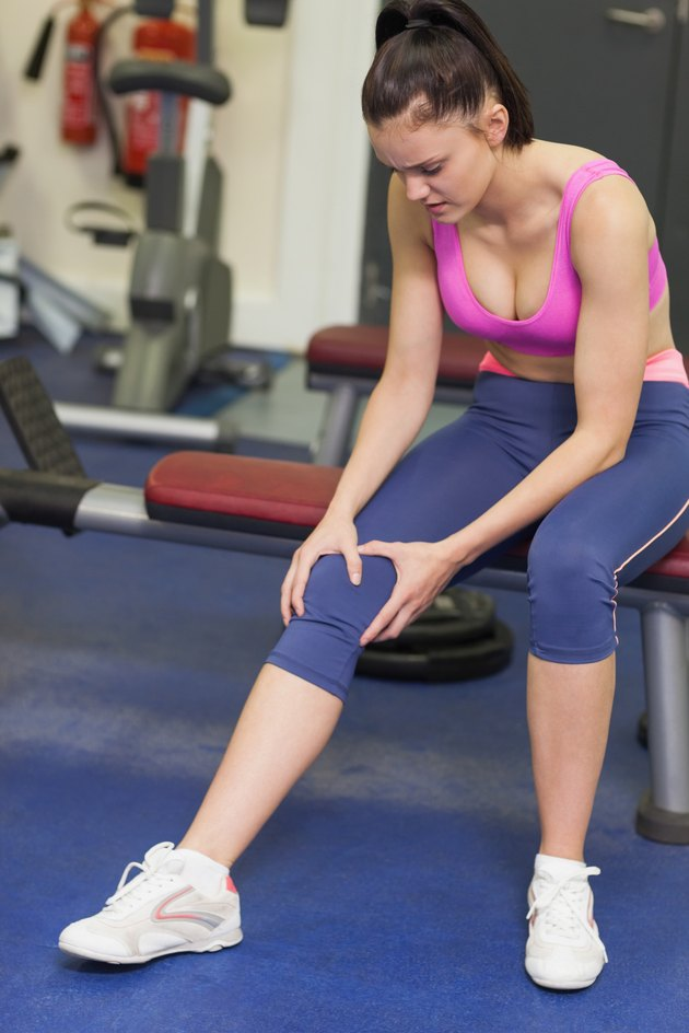 Healthy woman with an injured knee sitting in gym