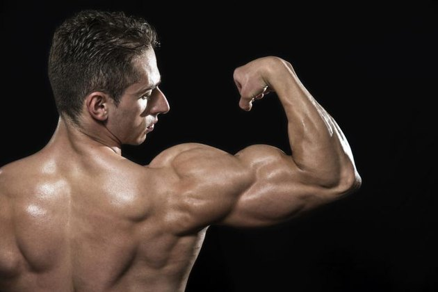 Young Bodybuilder Flexing Muscles - Isolated On Black Background - Copy Space