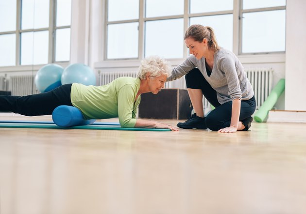 Physical therapist helping elderly woman in her workout