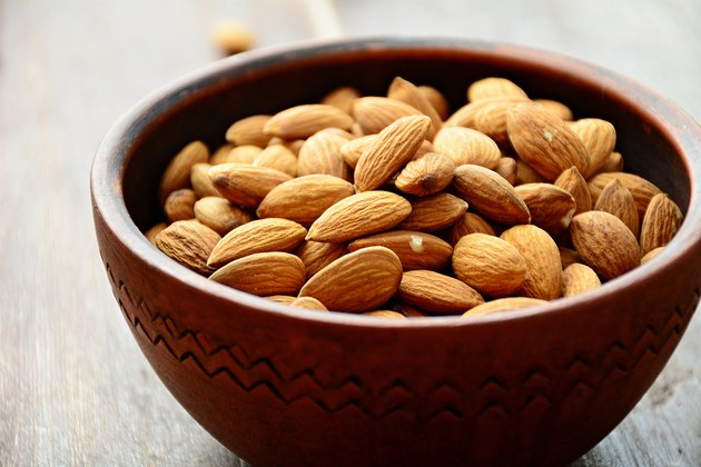 Almonds in ceramic bowl, raw food ingredients