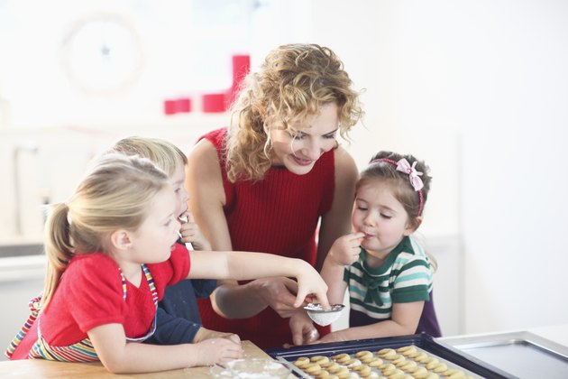Mid adult woman making cookies with son and daughters